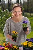 Mujer feliz que sostiene los potes con las flores del pensamiento Fotografía de archivo libre de regalías