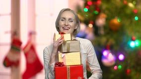 Mujer feliz que sostiene muchas cajas de regalo metrajes