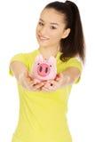 Mujer feliz que sostiene Piggybank Imagenes de archivo