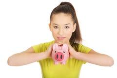 Mujer feliz que sostiene Piggybank Fotografía de archivo libre de regalías