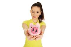 Mujer feliz que sostiene Piggybank Imagen de archivo libre de regalías