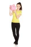 Mujer feliz que sostiene Piggybank Imagen de archivo