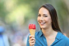 Mujer feliz que sostiene un helado que le mira Fotos de archivo