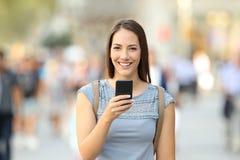 Mujer feliz que sostiene un teléfono que mira la cámara Foto de archivo libre de regalías