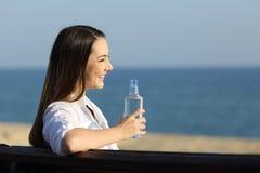 Mujer feliz que sostiene una botella de agua que mira horizonte Fotografía de archivo libre de regalías