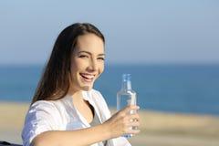 Mujer feliz que sostiene una botella de agua y que le mira al aire libre Foto de archivo libre de regalías