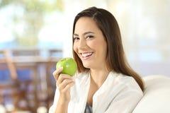 Mujer feliz que sostiene una manzana sana en casa Fotografía de archivo libre de regalías