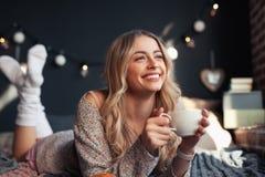 Mujer feliz que tiene bebida caliente en cama imagenes de archivo