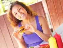 Mujer feliz que tiene Mini Hamburger Imagen de archivo libre de regalías