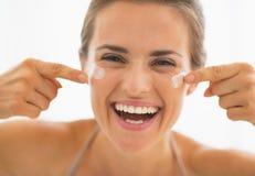 Mujer feliz que tiene tiempo de la diversión mientras que aplica la crema en cuarto de baño Fotos de archivo