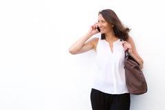 Mujer feliz que tiene una charla en el teléfono móvil Imagen de archivo