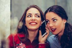 Mujer feliz que tiene una llamada de teléfono mientras que su mejor amigo que escucha su conversación fotografía de archivo libre de regalías
