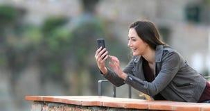 Mujer feliz que tiene una llamada video con un teléfono elegante