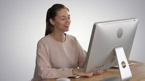 Mujer feliz que tiene una llamada video que se sienta delante de su ordenador en fondo de la pendiente almacen de video