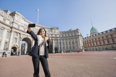 Mujer feliz que toma el autorretrato contra el arco del Ministerio de marina en Londres, Inglaterra, Reino Unido Fotografía de archivo