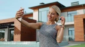 Mujer feliz que toma el selfie con llaves de la casa cerca de casa de lujo almacen de metraje de vídeo