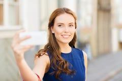 Mujer feliz que toma el selfie con smartphone en ciudad Foto de archivo libre de regalías