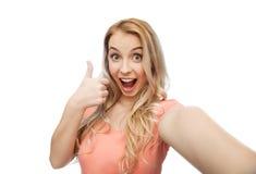 Mujer feliz que toma el selfie y que muestra los pulgares para arriba Imagen de archivo