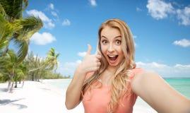 Mujer feliz que toma el selfie y que muestra los pulgares para arriba Foto de archivo