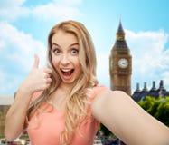 Mujer feliz que toma el selfie y que muestra los pulgares para arriba Foto de archivo libre de regalías
