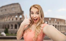 Mujer feliz que toma el selfie y que muestra los pulgares para arriba Imagen de archivo libre de regalías