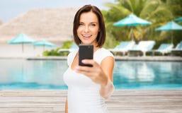 Mujer feliz que toma la imagen del smartphone sobre la playa Foto de archivo libre de regalías