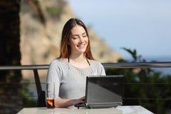 Mujer feliz que trabaja con su ordenador portátil en una terraza del hotel Imagen de archivo