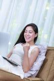 Mujer feliz que trabaja de hogar con el ordenador portátil Acción de los wi Imagenes de archivo