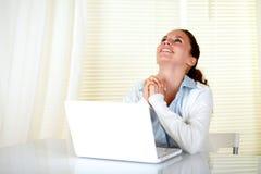 Mujer feliz que trabaja en la computadora portátil y que mira para arriba Imagenes de archivo