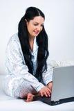 Mujer feliz que usa el cuaderno en cama Imagenes de archivo