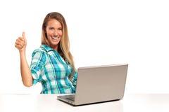 Mujer feliz que usa el ordenador portátil asentado en el escritorio Imagen de archivo