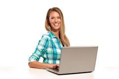 Mujer feliz que usa el ordenador portátil asentado en el escritorio Imagen de archivo libre de regalías