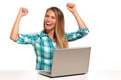 Mujer feliz que usa el ordenador portátil asentado en el escritorio Imagenes de archivo