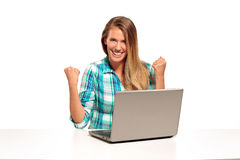 Mujer feliz que usa el ordenador portátil asentado en el escritorio Fotos de archivo libres de regalías