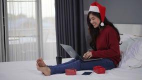 Mujer feliz que usa el ordenador portátil con el regalo de la Navidad en cama