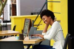 Mujer feliz que usa el ordenador portátil en el café Imagenes de archivo