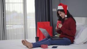 Mujer feliz que usa el ordenador portátil y sosteniendo el regalo de la Navidad en cama