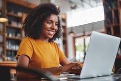 Mujer feliz que usa el ordenador port?til en caf? foto de archivo libre de regalías