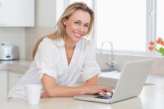 Mujer feliz que usa el ordenador portátil en el contador Imagenes de archivo