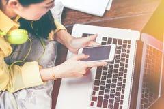 Mujer feliz que usa el teléfono y el ordenador portátil elegantes Efecto del vintage imagen de archivo