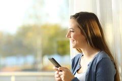 Mujer feliz que usa el teléfono y mirando lejos Imágenes de archivo libres de regalías
