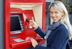 Mujer feliz que usa la atmósfera para retirar el dinero imagenes de archivo