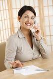 Mujer feliz que usa la calculadora Fotos de archivo