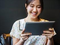 Mujer feliz que usa la PC de la tableta Fotografía de archivo