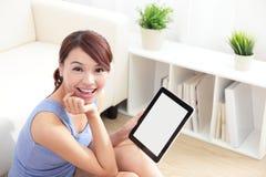 Mujer feliz que usa la PC de la tableta en el sofá Foto de archivo libre de regalías