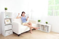 Mujer feliz que usa la PC de la tableta en el sofá Imagen de archivo