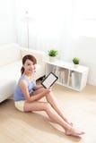 Mujer feliz que usa la PC de la tableta en el sofá Foto de archivo