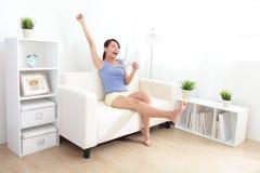 Mujer feliz que usa la PC de la tableta en el sofá Imágenes de archivo libres de regalías