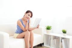Mujer feliz que usa la PC de la tableta en el sofá Imagenes de archivo