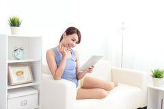 Mujer feliz que usa la PC de la tableta en el sofá Fotos de archivo libres de regalías